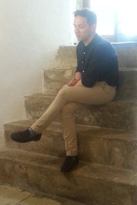 Iestyn Davies sitting on the steps at the Martello Tower, Landmark Trust