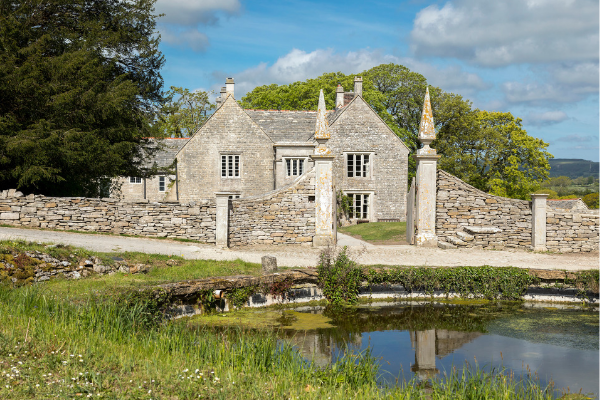 The exterior frontage of Dunshay Manor with a blue sky behind it. A pale grey stoned manor with two spiked stone gate piers. In the foreground is a pond.
